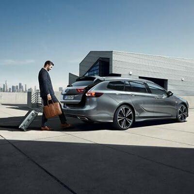 Mann mit Koffern vor grauem Opel Insignia